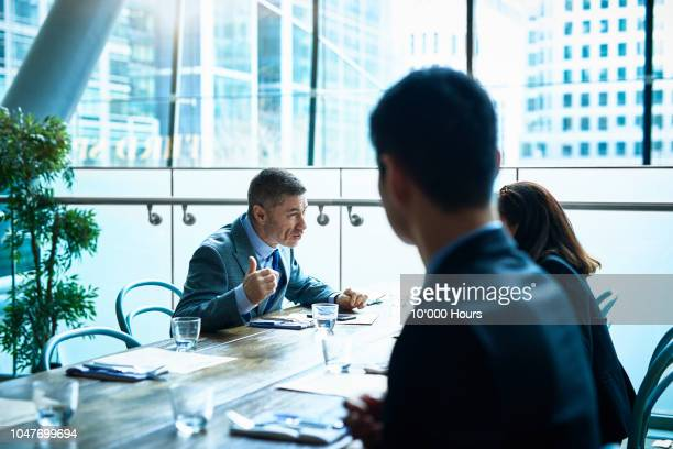 Mature man talking to colleagues in modern office