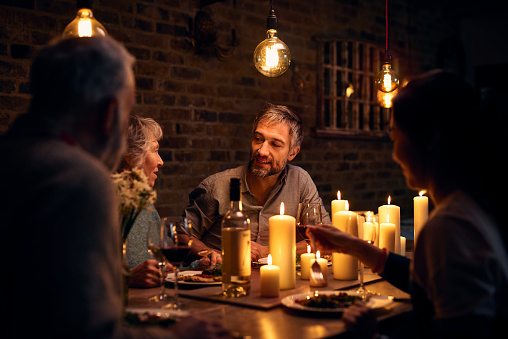 Mature man talking to friends at candlelit dinner table - gettyimageskorea