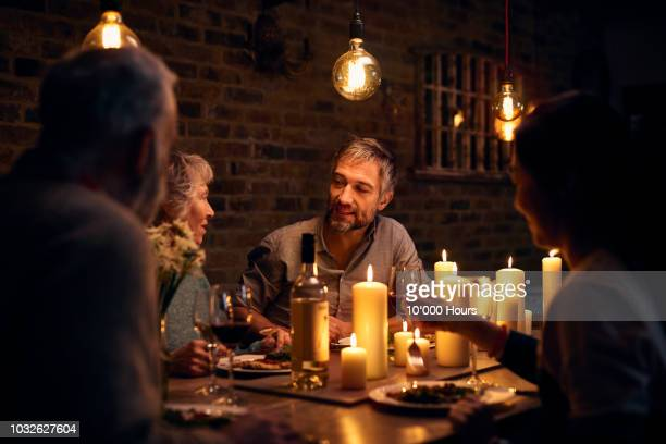 Mature man talking to friends at candlelit dinner table