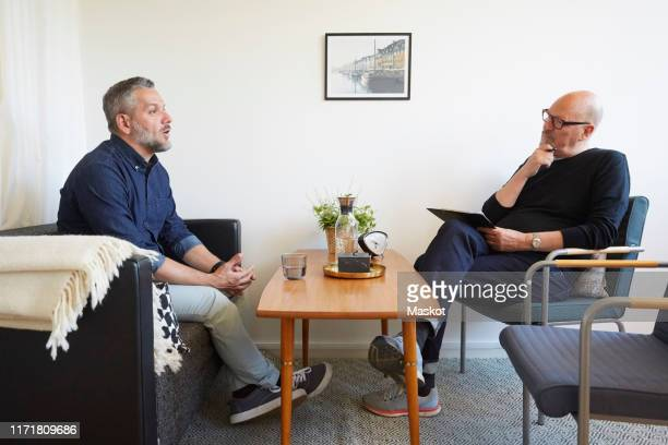 mature man talking to senior therapist at community center - mental health professional stock pictures, royalty-free photos & images