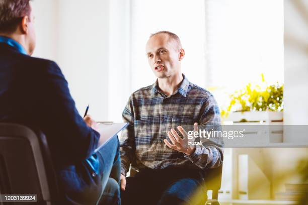 mature man talking with psychotherapist in his office - employment issues stock pictures, royalty-free photos & images