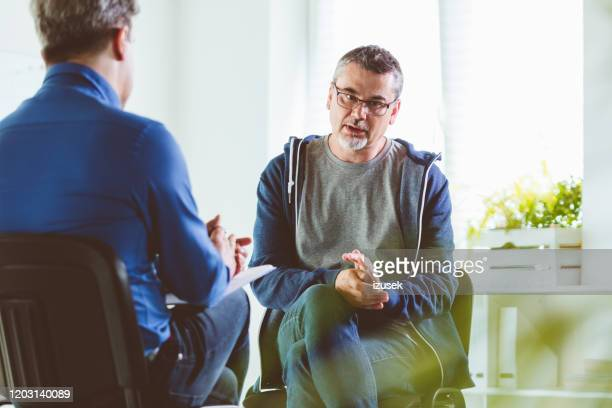 mature man talking with psychotherapist in his office - meeting stock pictures, royalty-free photos & images