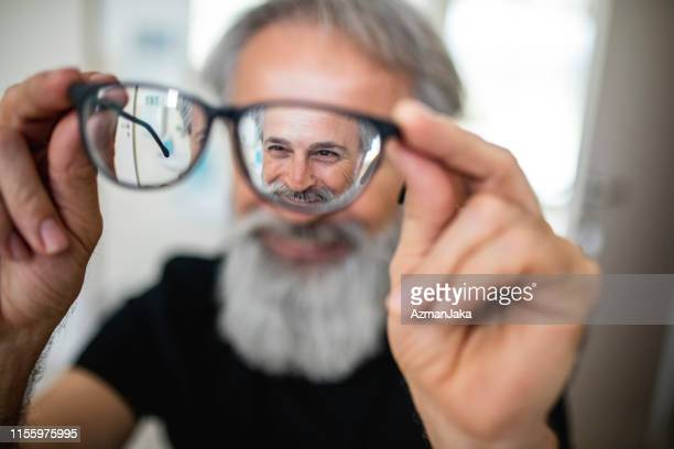 mature man testing out new glasses - eye care stock pictures, royalty-free photos & images