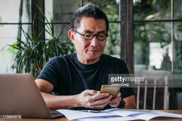mature man texting on cell phone with paperwork and laptop - financial bill stock pictures, royalty-free photos & images