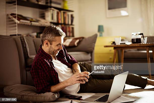 Mature man texting on mobile phone at home