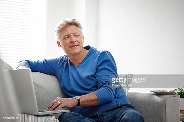 Mature man thinking while working on laptop