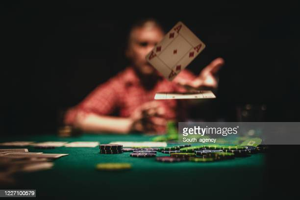 mature man throwing playing cards on table - competition stock pictures, royalty-free photos & images