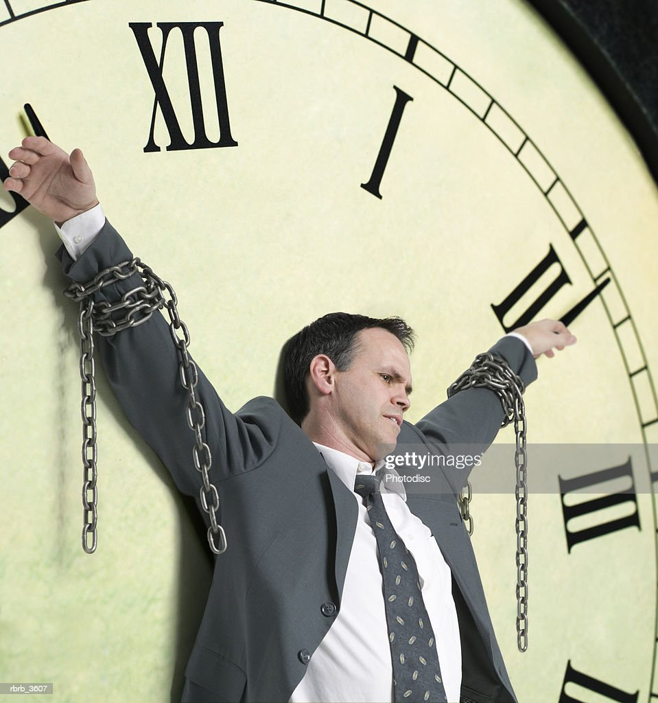 Mature man tied to a clock : Foto de stock