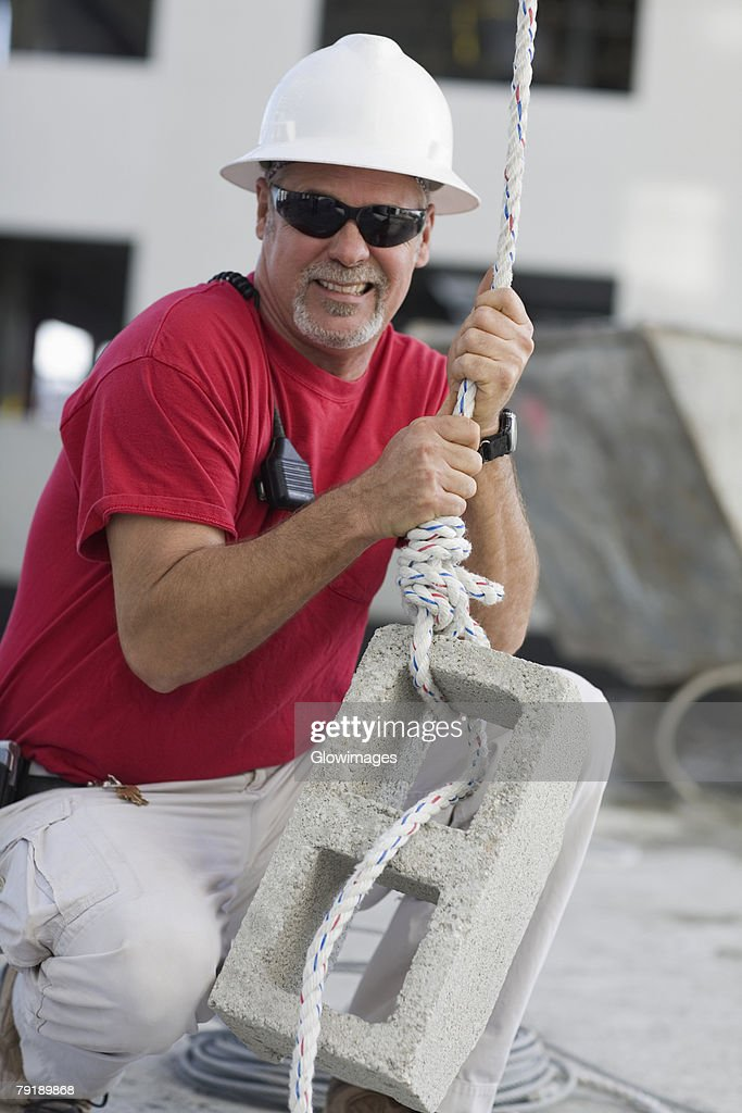 Mature man tightening a rope on a concrete block : Foto de stock