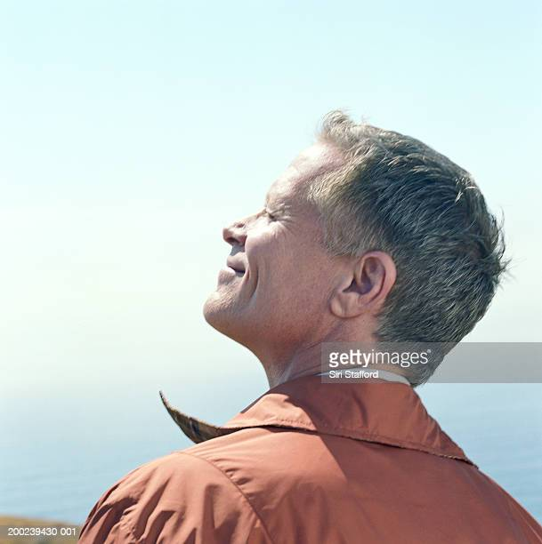 Mature man tilting head towards sun, profile