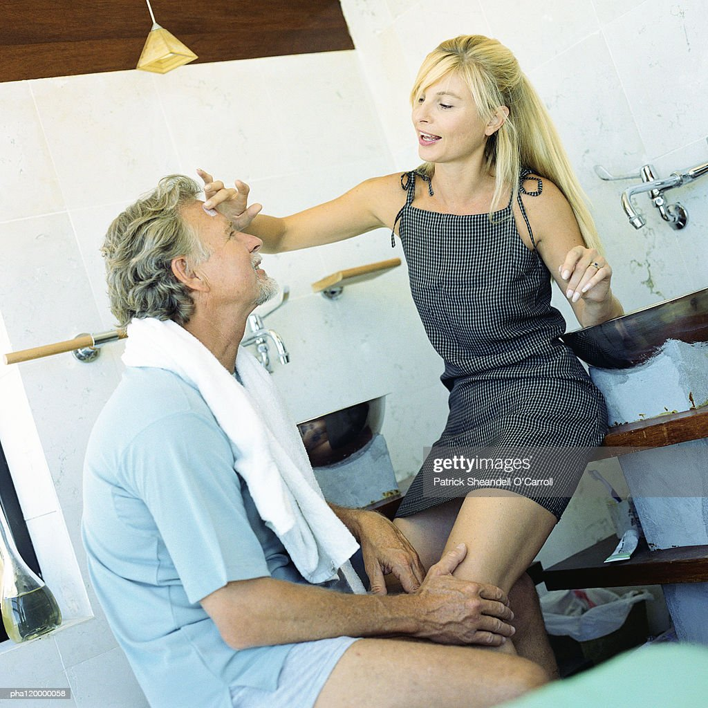 Mature man touching woman's legs : Stockfoto