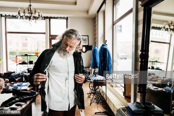 mature man trying on jacket in menswear store - black jacket stock pictures, royalty-free photos & images