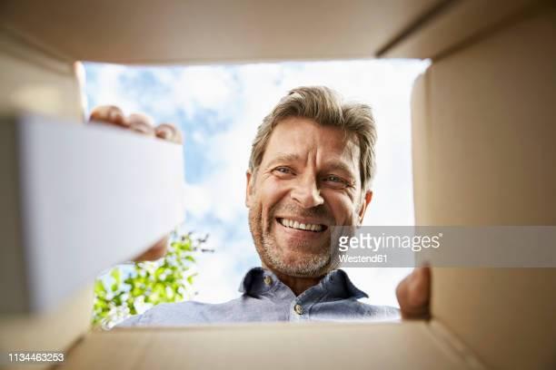 mature man unpacking delivery, looking into box, smiling - aufnahme von unten stock-fotos und bilder