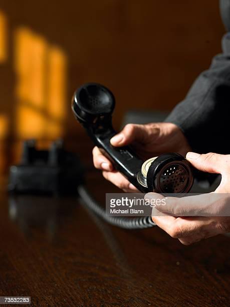 mature man unscrewing telephone receiver, close-up - 人体部位 ストックフォトと画像