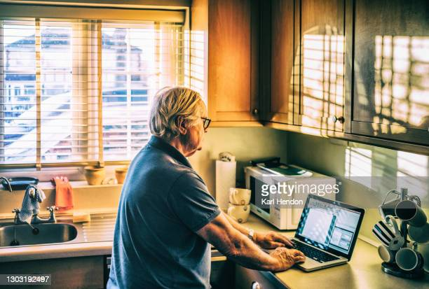 a mature man using a laptop in a suburban kitchen - stock photo - working seniors stock pictures, royalty-free photos & images