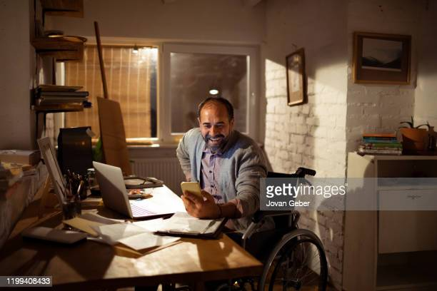 mature man using a phone in his office - persons with disabilities stock pictures, royalty-free photos & images