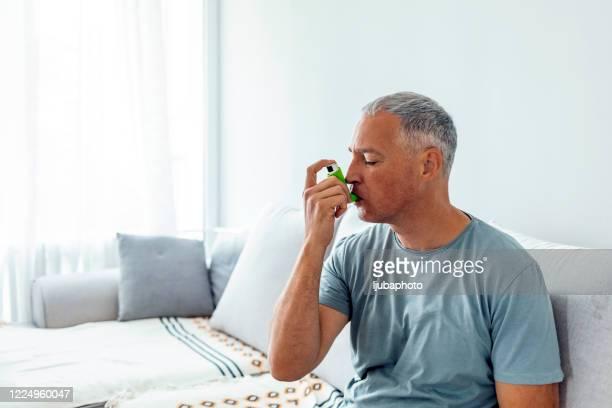 mature man using asthma pump - bomba para asma imagens e fotografias de stock