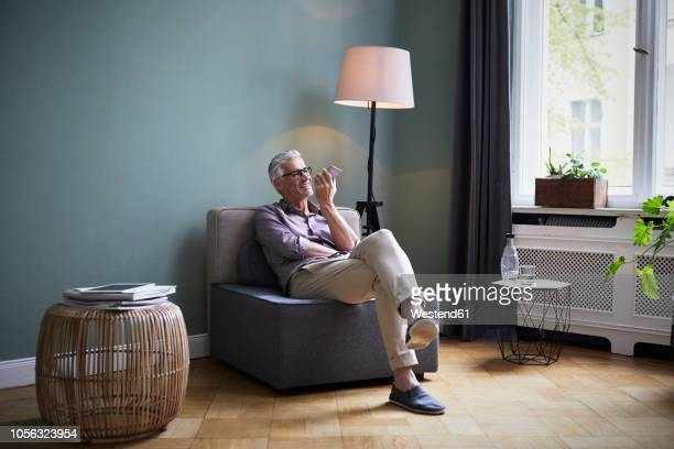 mature man using cell phone at home - armchair stock pictures, royalty-free photos & images