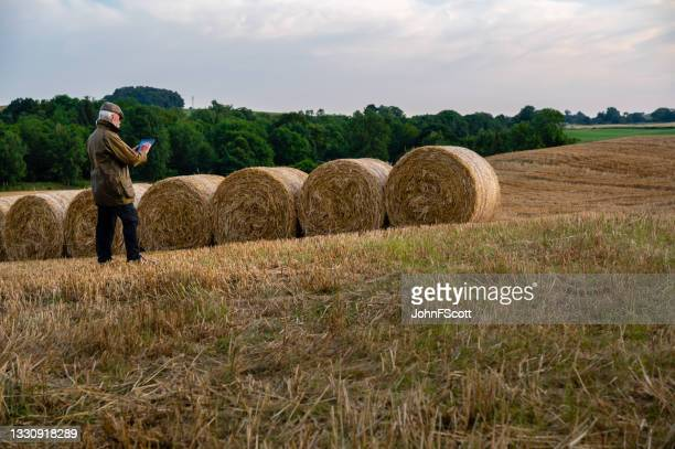 mature man using digital tablet after a harvest - johnfscott stock pictures, royalty-free photos & images