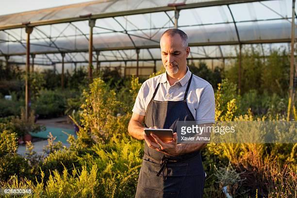 Mature man using digital tablet at garden center