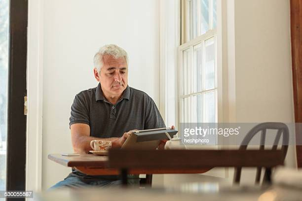 mature man using digital tablet in country store cafe - heshphoto stock pictures, royalty-free photos & images