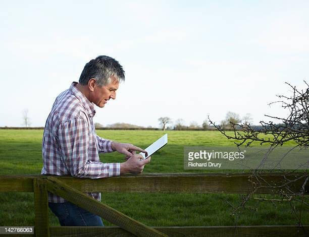 mature man using digital tablet in countryside - richard drury stock pictures, royalty-free photos & images