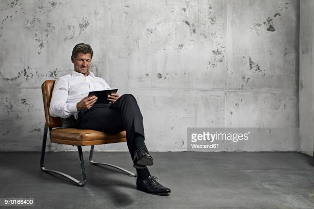 mature man using digital tablet in front of concrete wall - sitzen stock-fotos und bilder
