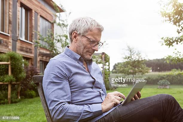 Mature man using digital tablet in garden