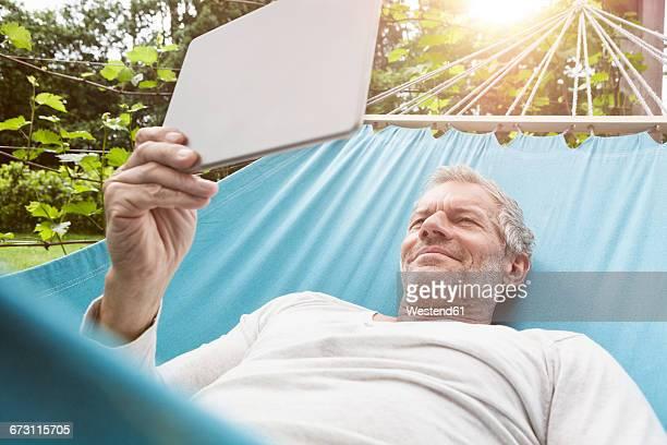 Mature man using digital tablet in hammock