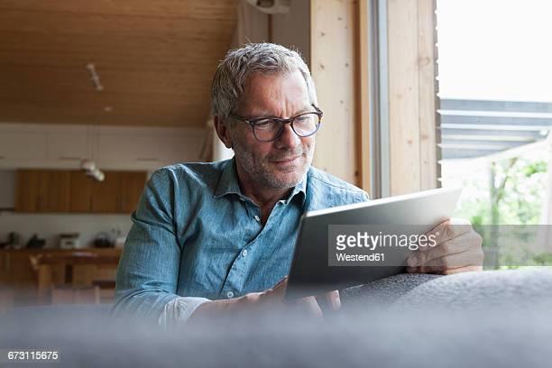 mature man using digital tablet on couch - tablet pc stock-fotos und bilder