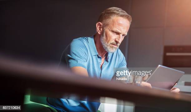 Reifer Mann mit digital-Tablette auf Tisch zu Hause