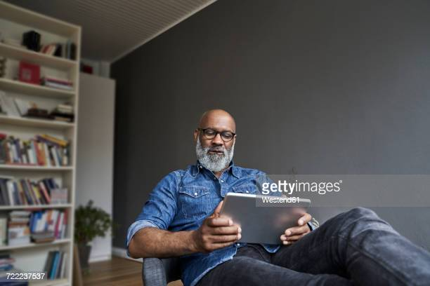 mature man using digital tablet - tablet benutzen stock-fotos und bilder