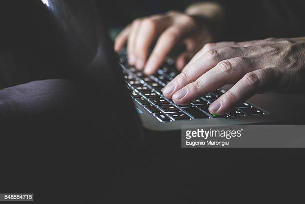 Mature man using laptop, focus on hands