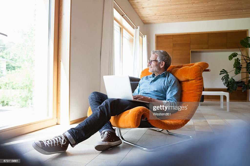 Mature man using laptop in armchair : Foto de stock