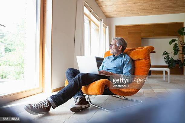 mature man using laptop in armchair - mature men stock pictures, royalty-free photos & images