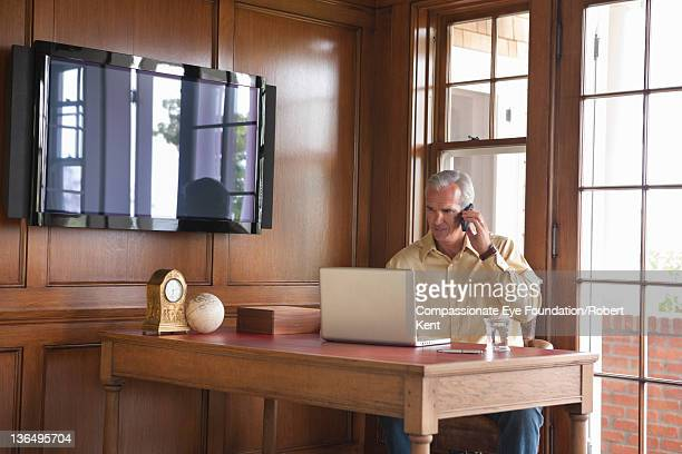 """mature man using laptop in home office - """"compassionate eye"""" stock pictures, royalty-free photos & images"""