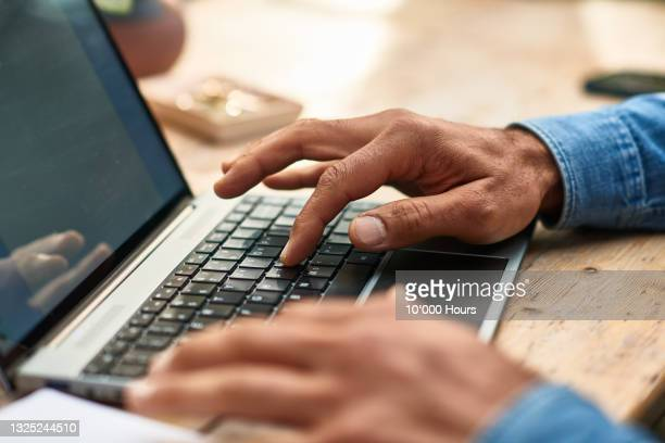 mature man using laptop keyboard close up - human finger stock pictures, royalty-free photos & images
