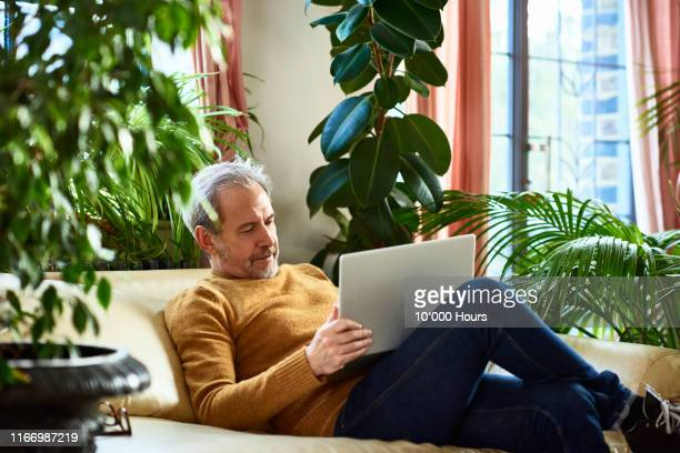 mature man using laptop on sofa at home - part of a series stock pictures, royalty-free photos & images
