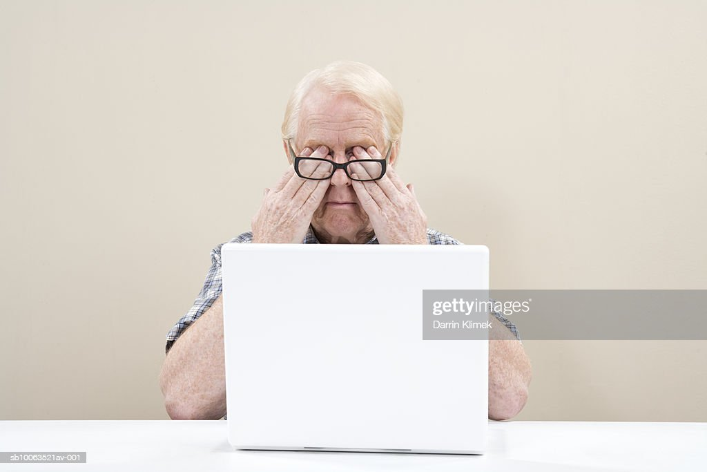 Mature man using laptop, rubbing eyes under spectacles : Stock Photo