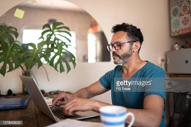 uomo maturo che usa il laptop per lavorare a casa - solo un uomo maturo foto e immagini stock