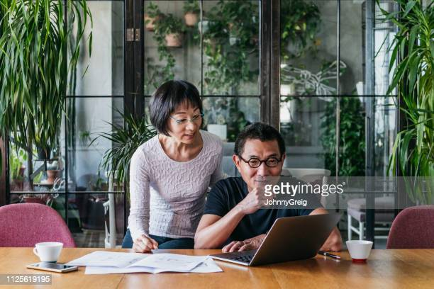 mature man using laptop with woman looking over shoulder - retirement stock pictures, royalty-free photos & images