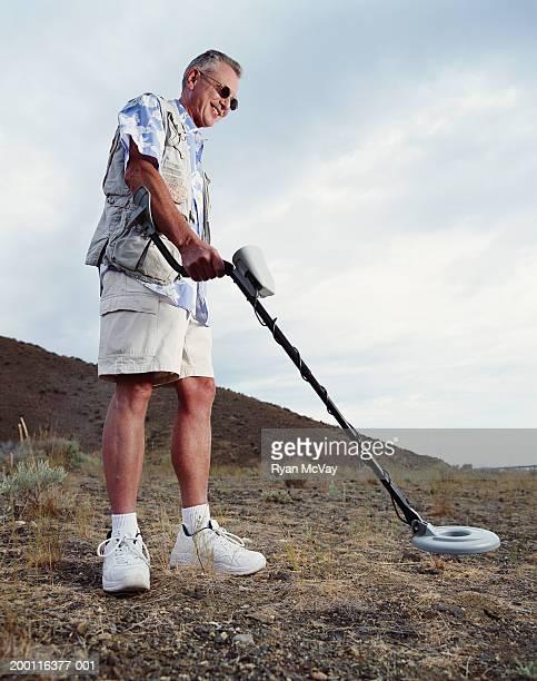 Mature man using metal detector, smiling