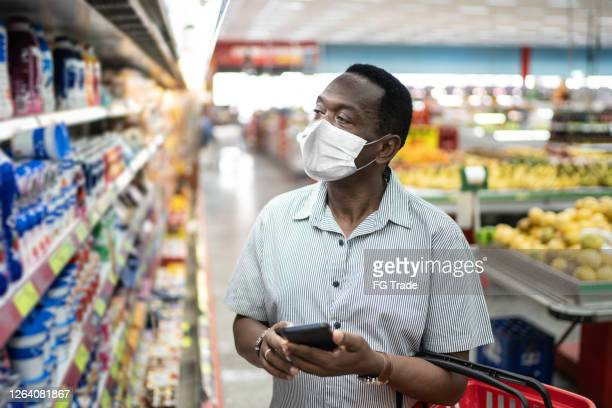 mature man using mobile and choosing products in supermarket - using face mask - brazil stock pictures, royalty-free photos & images