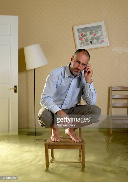 Mature man using mobile phone crouching on chair in flooded living room