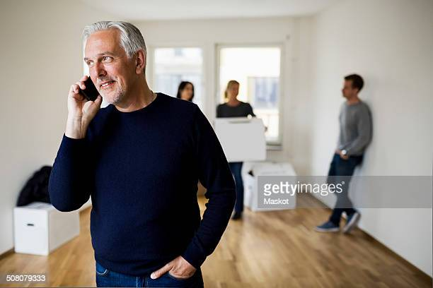 Mature man using mobile phone while family with moving boxes in background at home