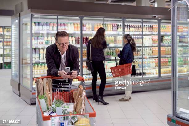 Mature man using mobile phone while leaning on shopping cart against women buying juices at refrigerated section in supe
