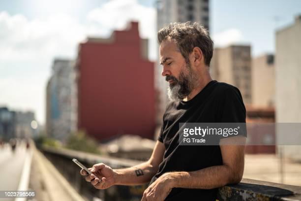 oudere man met behulp van mobiele portret op minhocao, sao paulo, brazilië - mobile stockfoto's en -beelden