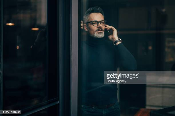 mature man using phone - suave stock pictures, royalty-free photos & images