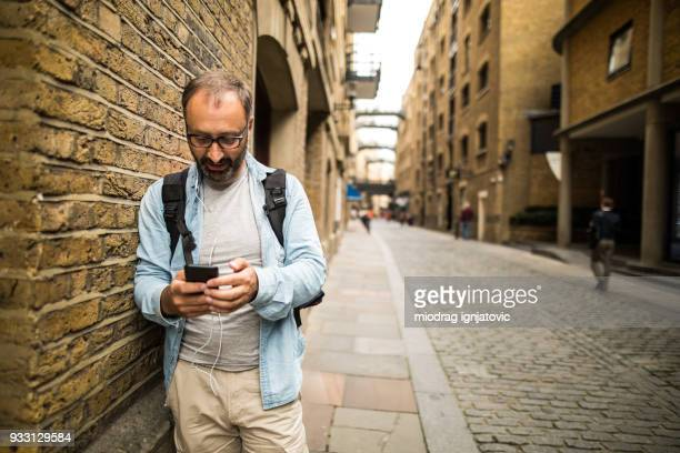 Mature man using smart phone outdoors