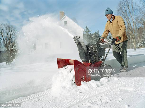 Mature man using snowblower outside home, winter